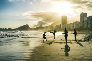 Football altinho silhouettes playing on the shore of Copacabana Beach at sunset in Rio de Janeiro, Brazil