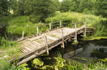 Old wooden bridge through stream