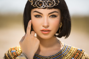 Beautiful woman with fashion make-up and hairstyle like Egyptian queen Cleopatra outdoors against desert
