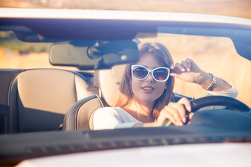 the girl sitting behind the wheel of a white convertible