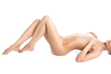 Close-up of torso of young seductive Caucasian model with long legs and perfect body lying on white background. Pretty person with healthy clean skin. Weight loss, healthy lifestyle concept. Studio