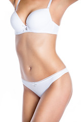 Close-up of torso of beautiful attractive Caucasian young woman wearing white set of lingerie. Fashion girl in white bra and panties standing against white background. Studio image