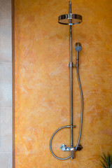 adjustable shower faucet hanging on yellow and orange bathroom wall