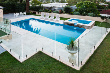 Modern swimming pool covered with glass panels beside a lawn