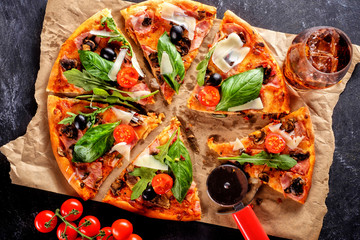 Homemade delicious pizza with bacon, tomatoes, olives and basil