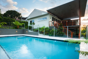 Luxury poolside closes up with modern house with green trees