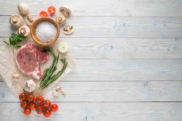 Raw pork cutlet with spices and Ingredients for grill or cooking on wooden background