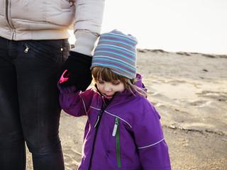 Little girl holding mothers hand