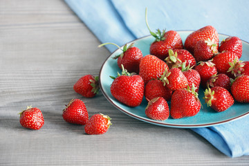 Ceramic plate with strawberries at old wooden table in daylight. Close up, high resolution product. Harvest Concept