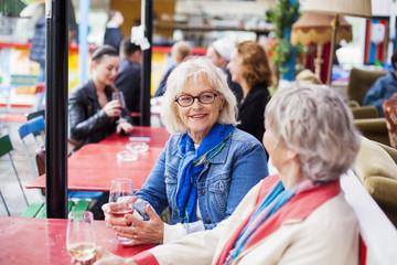 Senior women holding wineglasses while sitting at restaurant