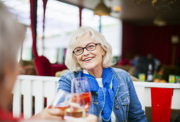 Senior women smiling and toasting wineglasses while sitting at restaurant