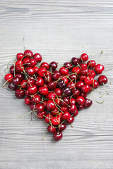Heart from berries of sweet cherry. Red cherry berries on wooden background. Top view, high resolution product