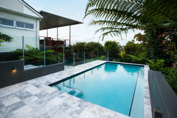Blue water swimming pool with floor tiles under green trees