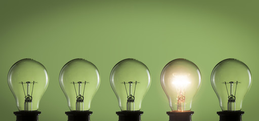 Idea concept. Light bulbs on green background