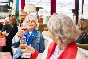 Senior women holding wineglasses while sitting at restaurant