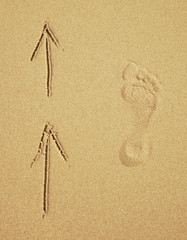 Trace of a human foot on sand. Tourist traffic.