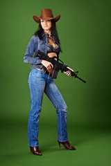 Beautiful woman in jeans with rifle on green