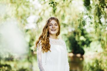 Portrait of happy female graduate at university park