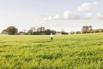 Mid distance of boy walking on grassy field against sky