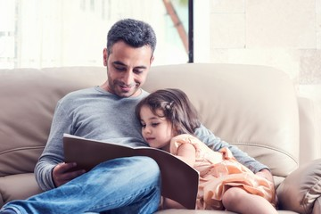 Little Girl And Father Reading Book Together