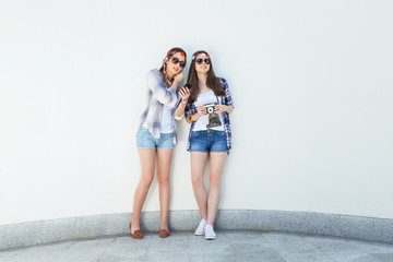 Two young hippie girls are standing in front of the white curved wall and listening to music. They wear matching outfits, plaid shirts and denim shorts, sunglasses and flowers hair accessories.