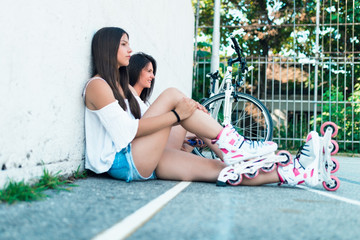 Two beautiful teenager girls enjoying beautiful sunny afternoon with bicycle and roller skates. City outdoors portraits.