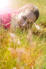 smiling beautiful teenage girl lying down, looking through the grass