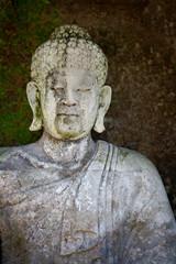 Old stone Buddha statue. Indonesia, Bali.