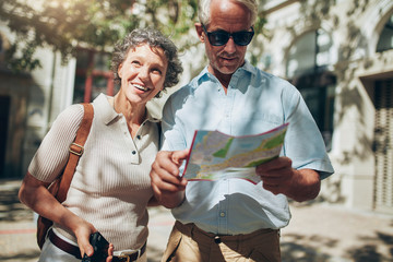 Mature man and woman using  map while sightseeing. Fototapete