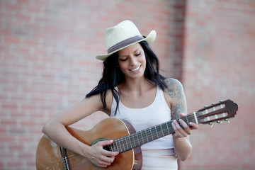 Brunette pretty woman playing a guitar