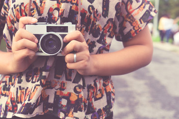 Close-up shot of woman hand holding retro camera. young hipster girl photographer with film camera - vintage filter color effect style