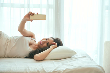 Young Asian woman taking selfie when lying in bed