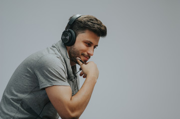 Portrait of a young handsome man face smiling on a grayed background with headphones listening to music