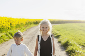 Portrait of smiling girl standing with brother at oilseed rape field