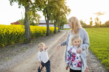 Happy family on dirt road at oilseed rape field