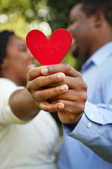 Loving African American couple holding a heart.