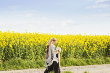 Rear view of mother and daughter walking at rapeseed field against sky