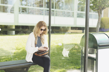 Young woman using phone while waiting at bus stop