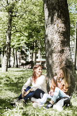 Women sitting against tree at grassy field at park