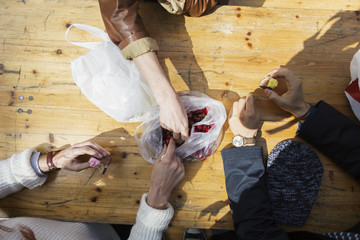 High angle view of friends eating cake and cherry while sitting on wooden table