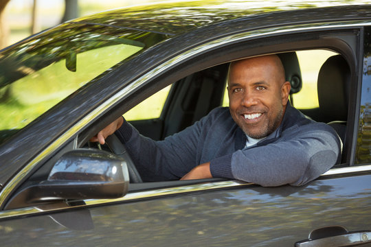 African American man driving  a new car.