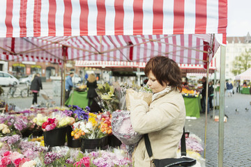 Side view of mature woman buying bouquet at flower stall