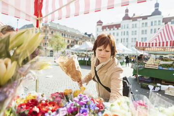 Mature woman buying bouquet at flower stall