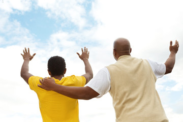 Father and teenage son with lifted hands.