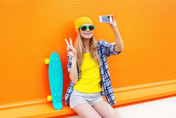 Fashion pretty cool girl makes self portrait on smartphone over