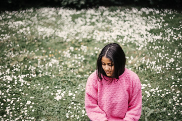 Happy young woman sitting on field in park