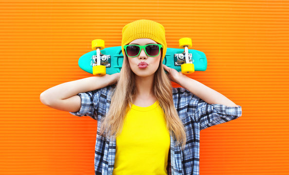 Fashion pretty cool girl with skateboard over colorful orange ba