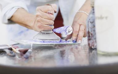 Midsection of senior female painter using printing block in studio