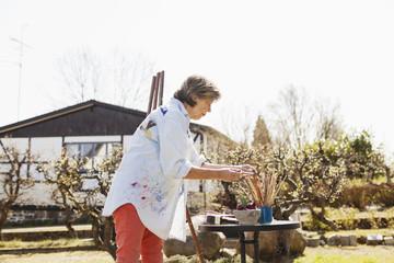 Side view of senior female painter working outside art studio