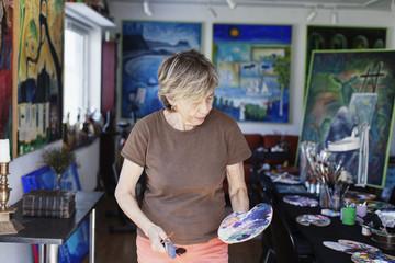 Senior female artist holding palette and paint brushes in studio